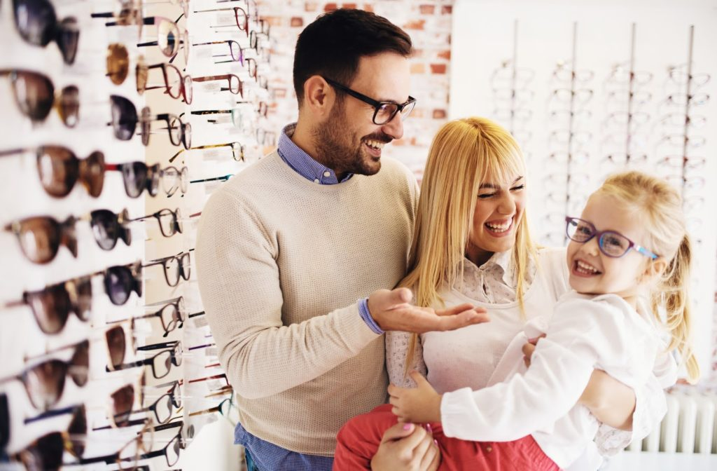 Happy family choosing glasses for daughter at optometrist office.