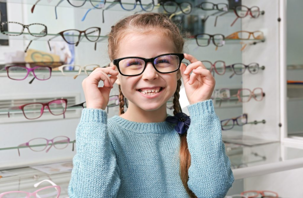 Happy girl at optometrist office trying on different glasses